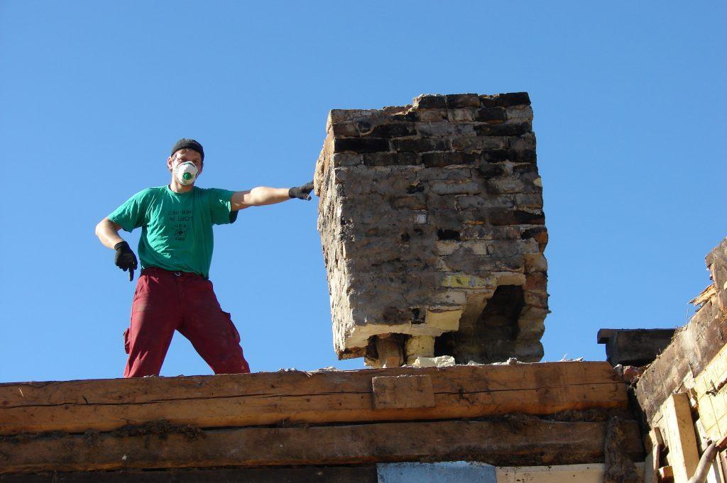 Statybininkas griauna namo kaminą