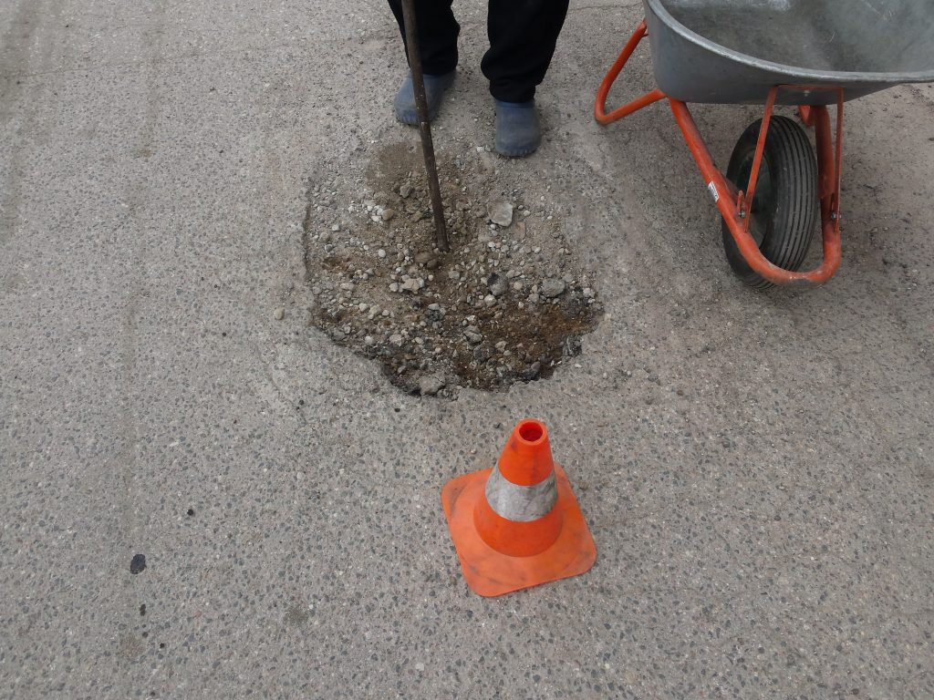 šlapias asfaltas duobėje